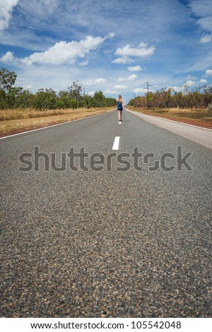 Woman is going through the road of outback, Outback Australia, Northern Territory - stock photo