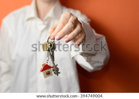 woman is handing a house key. Key with a key chain in the shape of house - stock photo