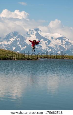 Woman is happy -  she has given a skip for joy. This action comes near mountain lake (Caucasus Mountains, Georgia, Mestia region). - stock photo