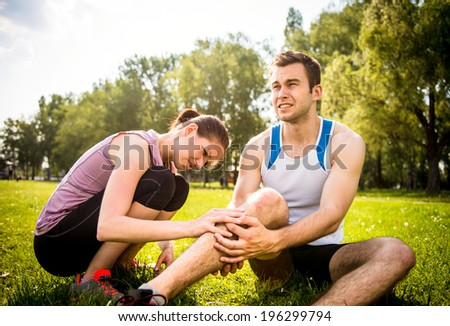Woman is helping to young man with injured calf from jogging - stock photo
