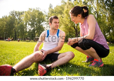 Woman is helping to young man with injured thigh from sport activity - stock photo