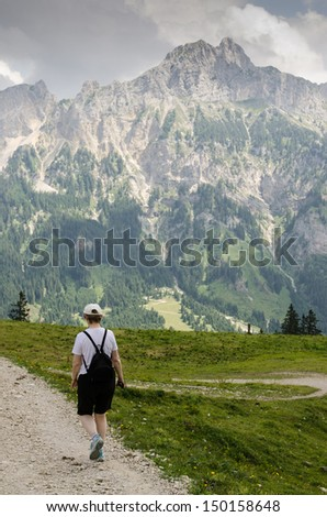 Woman is hiking on a trail in the mountains - stock photo