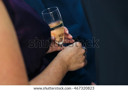 Woman is holding a goblet of the champagne on the wedding