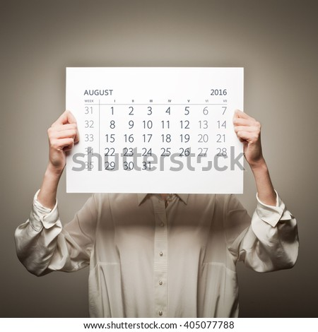 Woman is holding August calendar of the year two thousand sixteen.