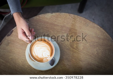 woman is holding cup of coffee. - stock photo