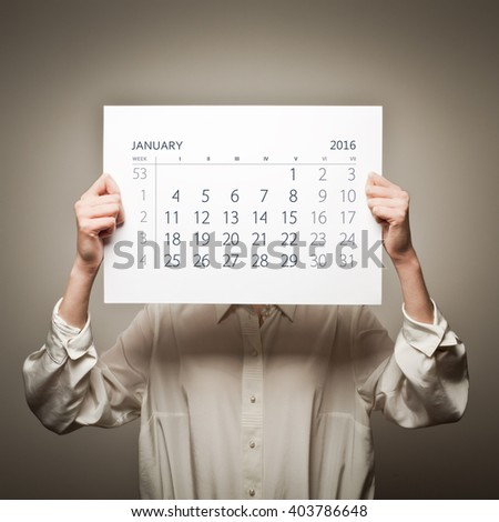 Woman is holding January calendar of the year two thousand sixteen. - stock photo