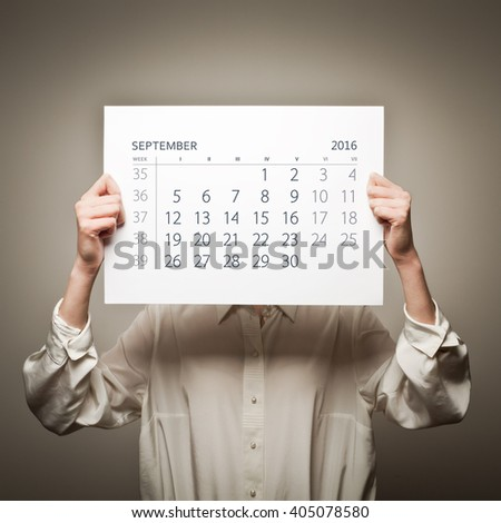 Woman is holding September calendar of the year two thousand sixteen.