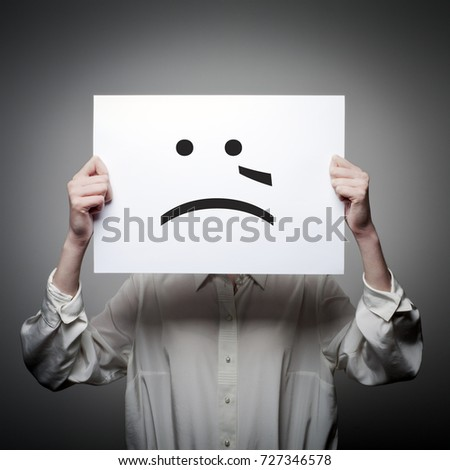 Woman is holding white paper with smile. Crying and trouble concept.