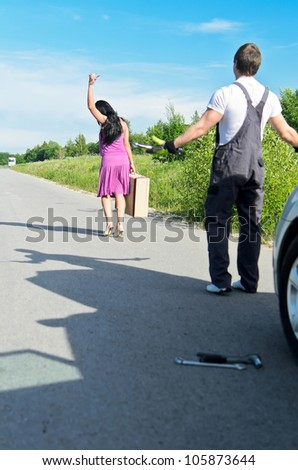 Woman is leaving mechanic alone near the broken car. - stock photo