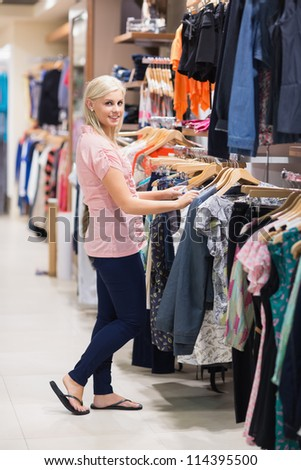 Woman is looking at clothes searching and smiling - stock photo