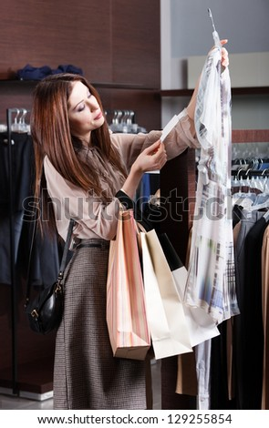 Woman is looking for a perfect inexpensive cloth - stock photo