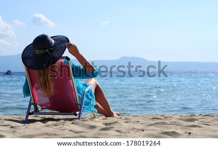 Woman is lying on a deck chair - stock photo
