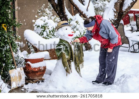 Woman is making a snowman in her front yard during snow storm - stock photo