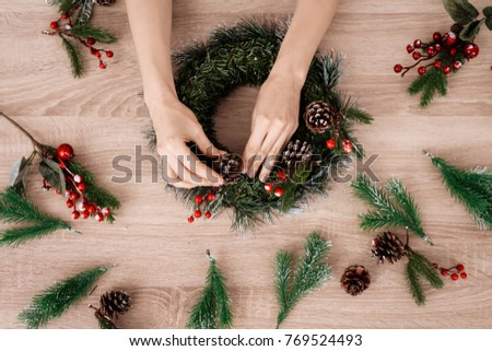 Woman is making jewelry for the Christmas holidays. Girl is engaged in the manufacture of wreaths.