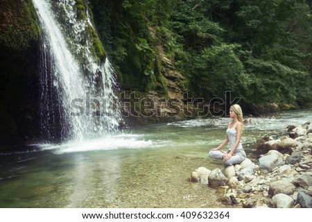 Woman is meditating near the waterfall and river.