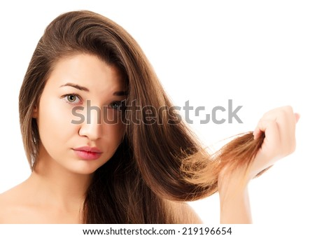 woman is not happy with her fragile hair, white background, copyspace  - stock photo
