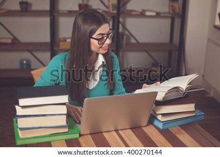 Woman is opened a book. She is working with lots of books and laptop at the wood table
