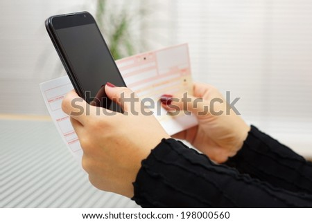 Woman is paying bill on mobile smart phone - stock photo
