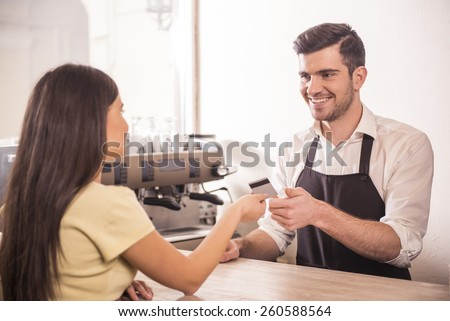 Woman is paying for coffee by credit card. - stock photo