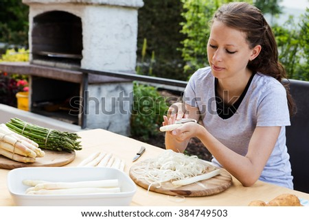 woman is peeling green and white asparagus