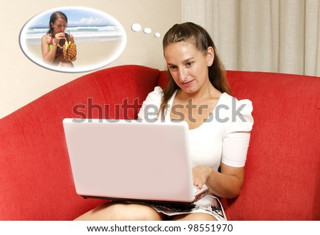 Woman is planning her vacations on her laptop. She dreams about going to the beach. - stock photo