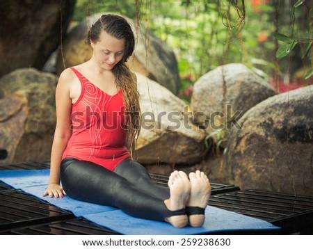 Woman is practicing yoga outdoor. Staff pose. Dandasana - stock photo
