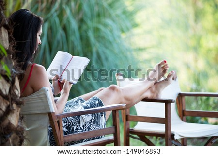 Woman is reading a book in the idyllic garden