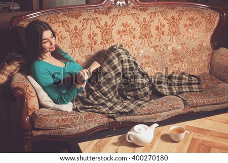Woman is reading a book on the sofa with 