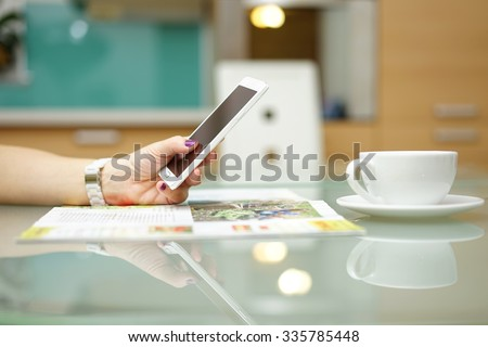 Woman is reading magazine and surfing on the internet on smart mobile phone in the kitchen - stock photo