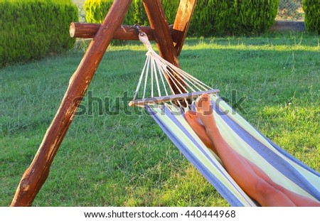 Woman is relaxing in a hammock in a natural landscape