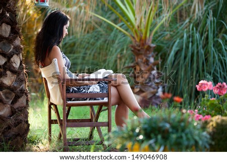 Woman is relaxing in a tropical garden reading a book - stock photo