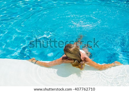 Woman is relaxing in swimming pool at the summer resort - stock photo