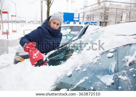 Woman is removing snow from car window with ice scraper in winter.