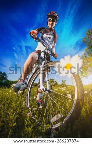 Woman is riding bicycle outside - stock photo