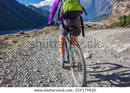 Woman is riding mtb bike in Himalaya mountains, Anapurna region - stock photo