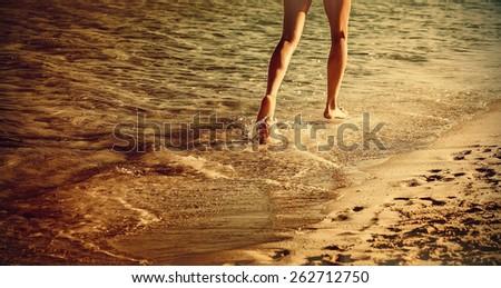 Woman is running ahead on beach of sea. Orange sunset. Legs close-up - stock photo