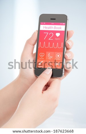 Woman is scanning heartbeat cardiogram by modern smartphone with health book app on the screen. - stock photo