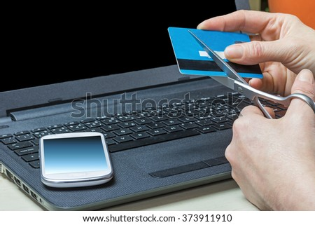 Woman is sheering a credit card by scissors. White smart phone is lying on the dark notebook. All potential trademarks are removed.  - stock photo