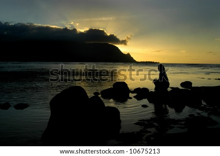 Woman is silhouetted as she sits on rocks in bay at Princeville Resort.  Sun is setting behind mountain and reflecting in water. - stock photo