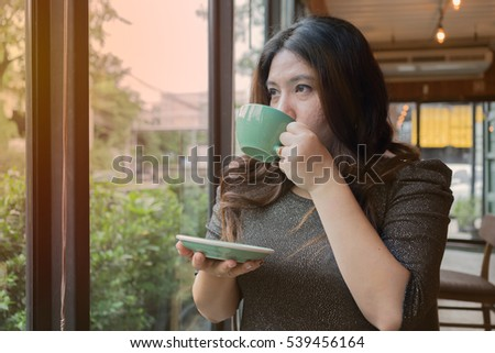 woman is sipping drinking hot coffee at coffee time at coffee shop or home in garden view and relax atmosphere / woman and coffee