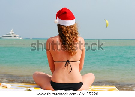 woman is sitting near sea in santa hat