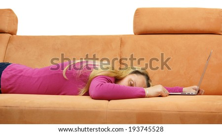 woman is sleeping on the couch after working on her laptop computer - stock photo