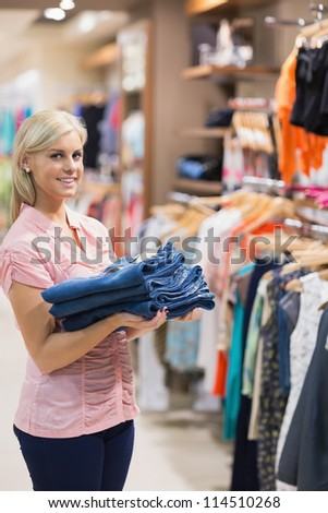 Woman is standing in a shopping mall holding pants in her hands smiling - stock photo