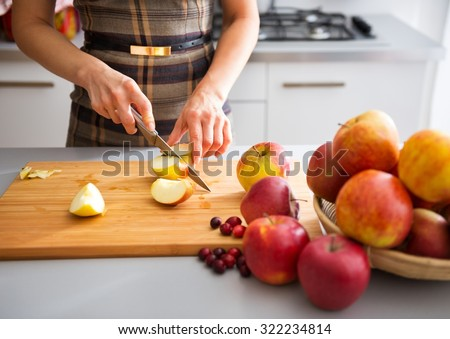 Woman is standing in her kitchen, preparing apples to use to make applesauce and other fruit preserves - stock photo
