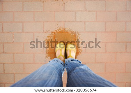 woman is standing in the wet floor among the rain under the reflection of umbrella ,selective focus - stock photo