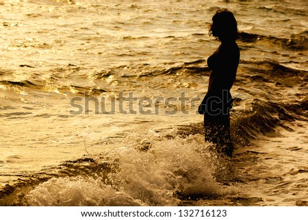 Woman is standing near the sea. Sunset