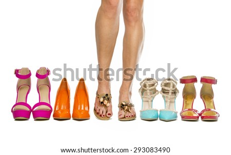 Woman is standing with slippers or flip-flops in between a group of fashionable high heels shoes. - stock photo
