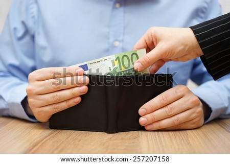 Woman is taking money out of a husband's wallet - stock photo