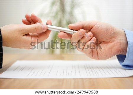 Woman is taking pen from businessman to sign the document - stock photo