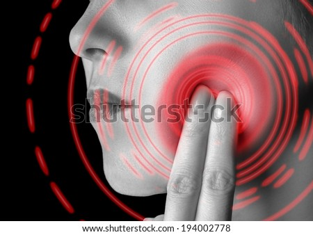 Woman is touching her cheek, toothache, pain area of red color, monochrome image - stock photo